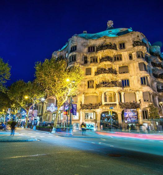 BARCELONA-NOVEMBER 24: La Pedrera or Casa Mila at dusk, built and designed by Antoni Gaudi, with traffic lights, on November 24, 2012, Barcelona, Spain